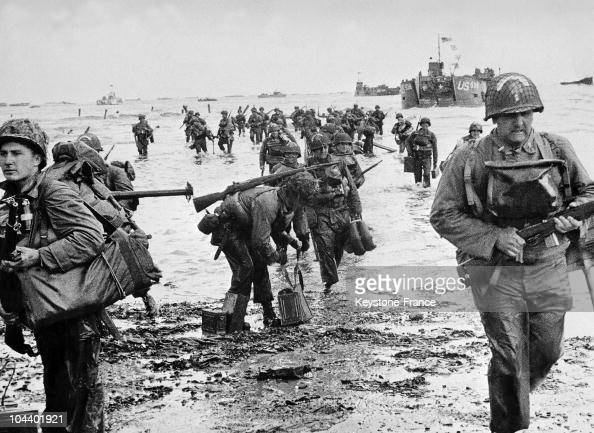 American soldiers their feet in water are landing on a Normandy beach In the background are the American military ships which transported them