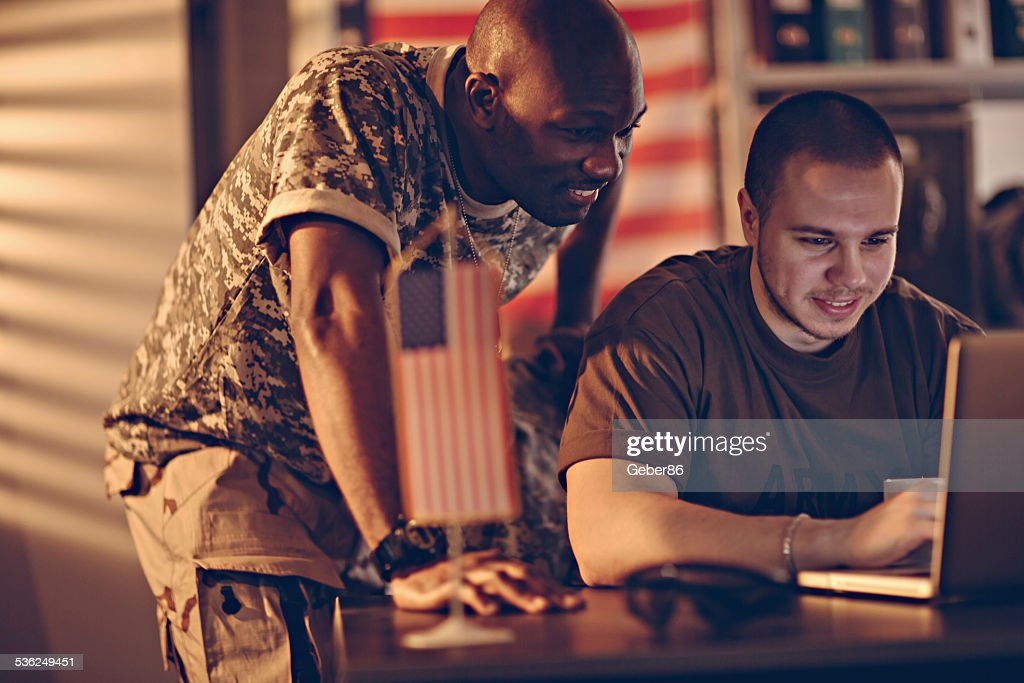 American soldiers using laptop : Stock Photo