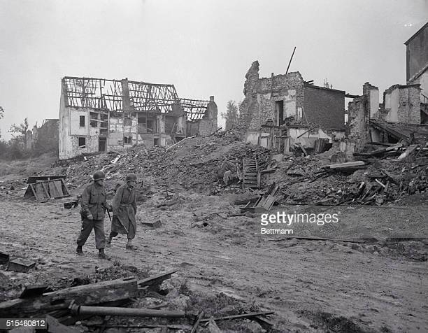 American soldiers walk through the rubble and debris of a street in AachenForst which is approximately 150 yards from the Nazi stronghold at Aachen...