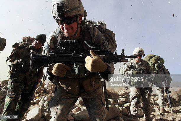 American soldiers with the Army 3rd Battalion 509th Parachute Infantry Division and Afghan National Army soldiers turn away from debris during the...