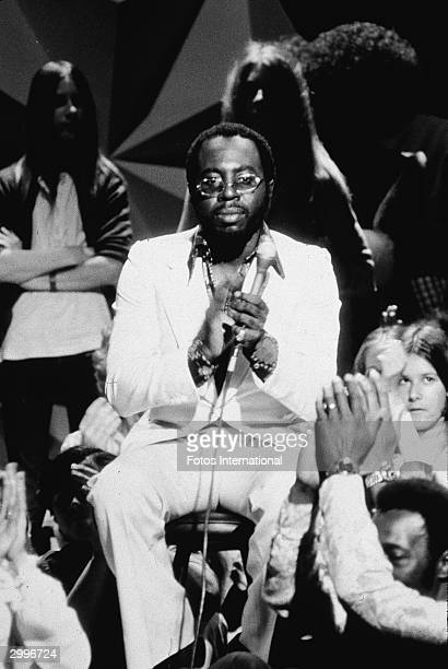 American soul singer and songwriter Curtis Mayfield sits with a crowd during an appearance on the TV concert series 'Midnight Special' 1970s