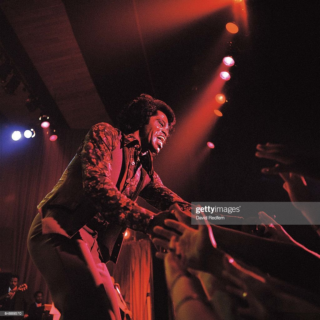 VENUE Photo of James BROWN and AUDIENCE, performing live onstage, touching hands with the audience, fans