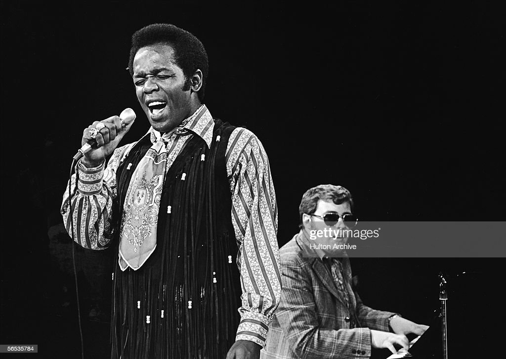 American soul singer Lou Rawls (1935 - 2006) closes his eyes as he sings with a pianist accompanying him on stage, 1970s.