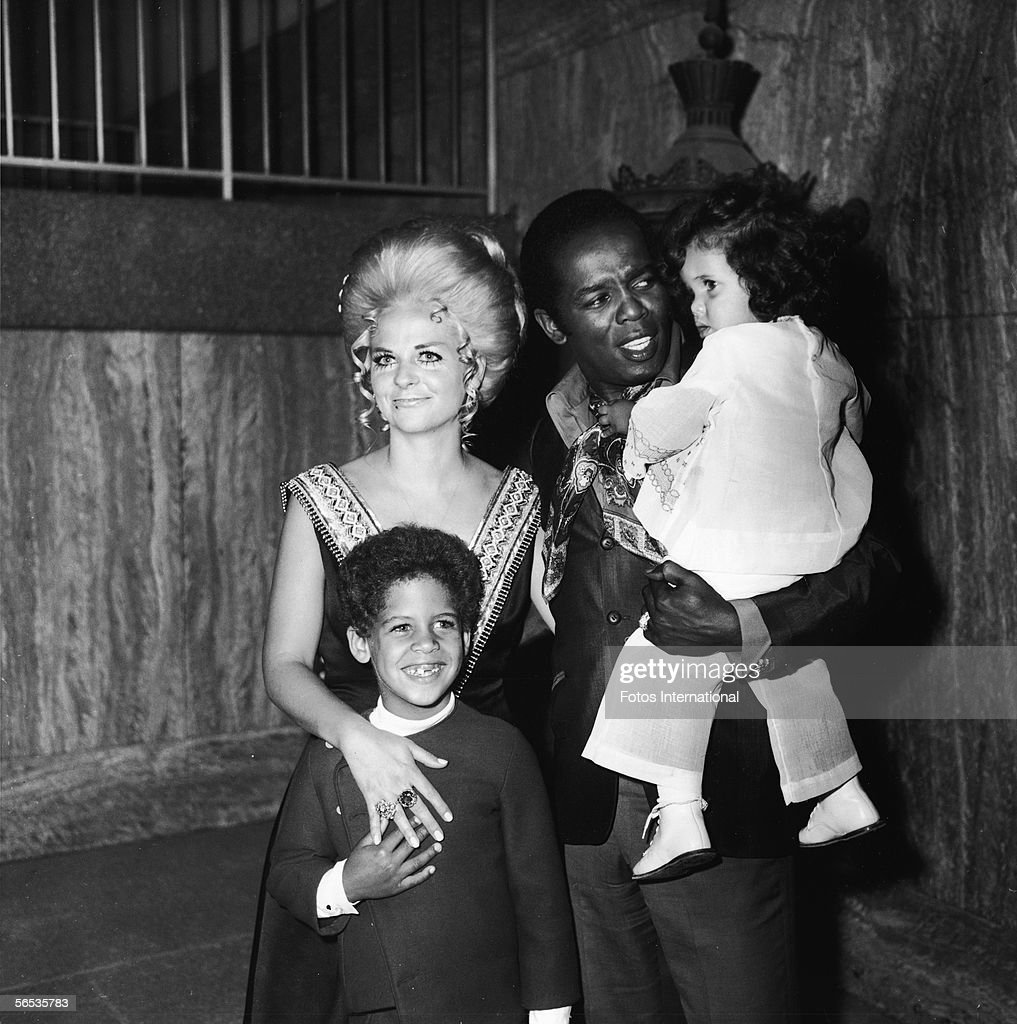 American soul singer Lou Rawls (1935 - 2006) holds his daughter Louanna as his wife Lana Jean and son Lou Jr. stand with him at the opening of his stint at the Century Plaza Hotel, Los Angeles, California, 1973.