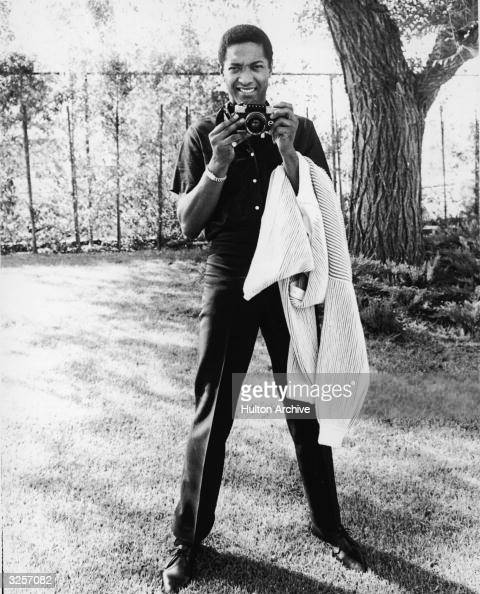 American soul singer Sam Cooke gets ready to take a photograph while he holds a sweater over his left arm early 1960s