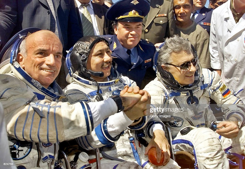American space tourist Dennis Tito, left, and Russian cosmonauts Talgat Musabayev, center, and Yuri Baturin join hands after their landing May 6, 2001 near Arkalyk, Kazakstan. Tito was returning from a six-day voyage to the International Space Station, a trip for which he paid $20 million.