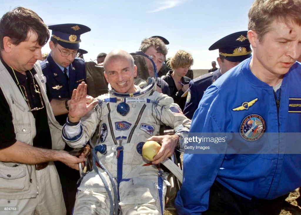 American space tourist Dennis Tito, 60, waves as he is helped into a wheelchair shortly after landing inside the Russian Soyuz space capsule May 6, 2001 near Arkalyk, Kazakhstan. Tito was returning from a six-day voyage to the International Space Station, a trip for which he paid $20 million.