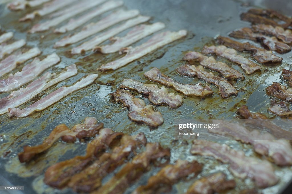 American streaky bacon is seen cooking on a griddle in the kitchen at the first U.K. outlet of U.S. burger restaurant chain Five Guys in London, U.K., on Tuesday, July 2, 2013. Five Guys, which is set to open its first U.K. store in Covent Garden on July 4, is a family outfit that started in Washington, D.C., in 1986, and has expanded to more than 1,000 locations in the U.S. and Canada. Photographer: Simon Dawson/Bloomberg via Getty Images