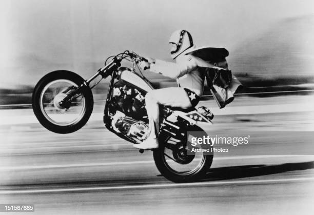 American stunt rider Evel Knievel pulls a wheelie on his Harley Davidson motorcycle circa 1975