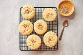 American style round cookies with confetti (shortbread) on a wire rack on a grey stone backdrop.