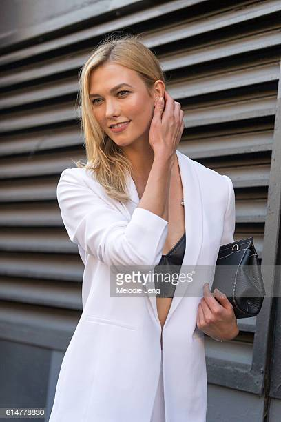 American supermodel Karlie Kloss attends the Boss Women show in a white Hugo Boss blazer black bralette top and black purse at Skylight Clarkson Sq...