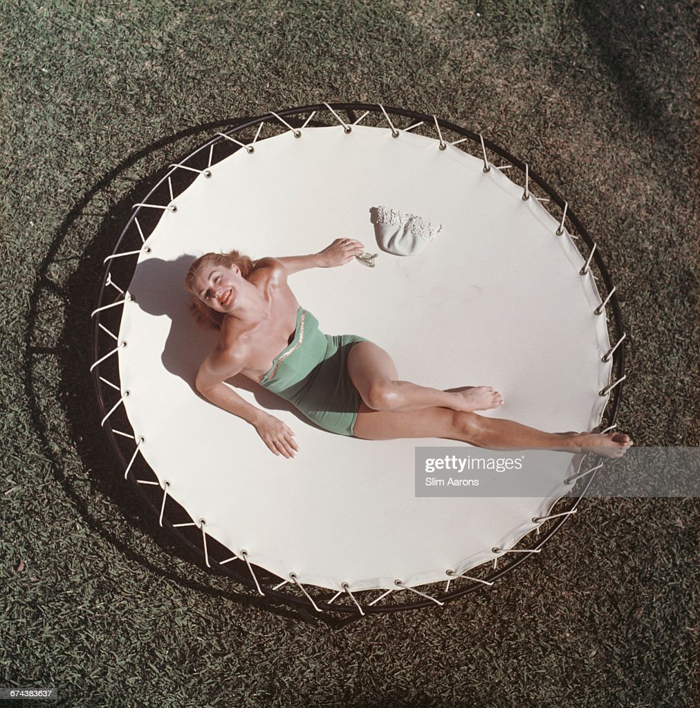 American swimmer and actress Esther Williams lounging on a trampoline circa 1956