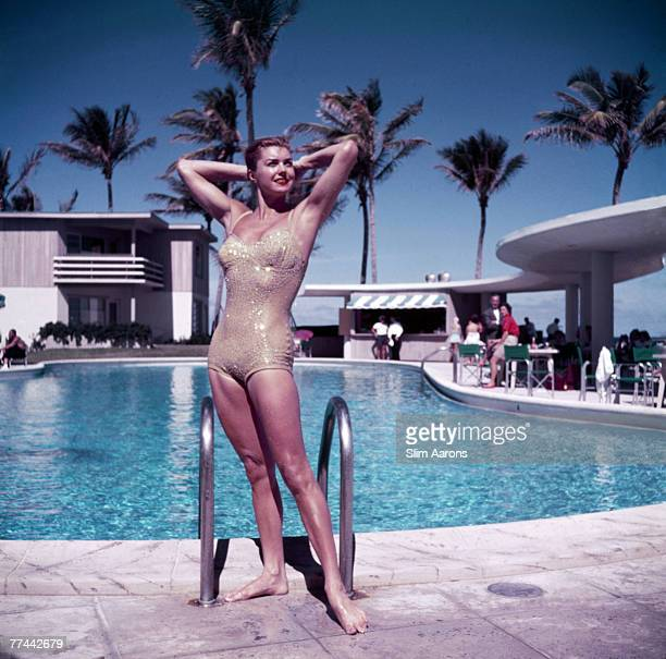 American swimmer and actress Esther Williams posing by the pool in a sparkly gold swimsuit Florida 1955