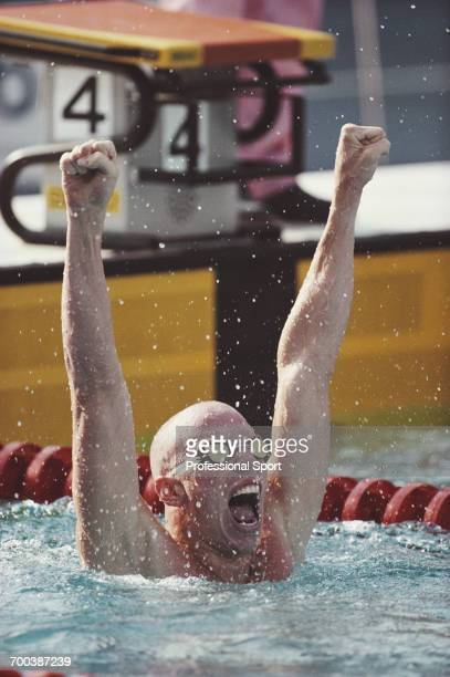 American swimmer Nelson Diebel pictured with his arms in the air in celebration after finishing in first place in an Olympic record time of 1 minute...