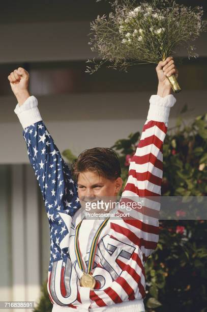 American swimmer Nicole Haislett celebrates as she stands on the podium after finishing in first place to win the gold medal for the United States...