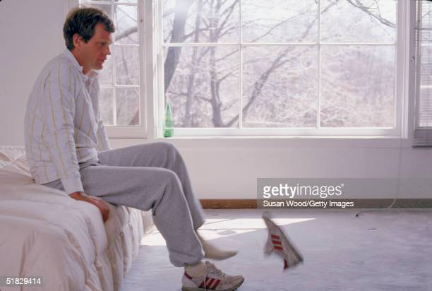 American talk show host David Letterman kicks off his shoes while sitting on his bed Westchester County New York March 1984