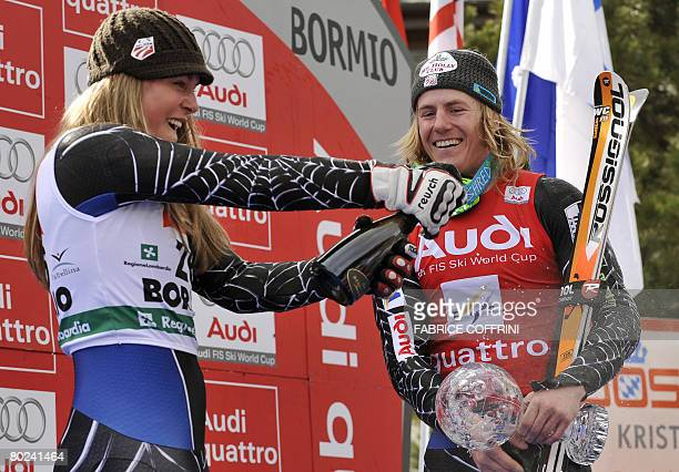 American Ted Ligety holds his globe as compatriot Lindsey Vonn spray's champagne on the podiumafter the men's Giant Slalom second run at the FIS Ski...