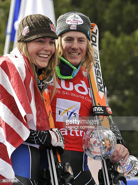 American Ted Ligety holds his globe as he poses with compatriot Lindsey Vonn during the men's Giant Slalom second run at the FIS Ski World Cup Grand...