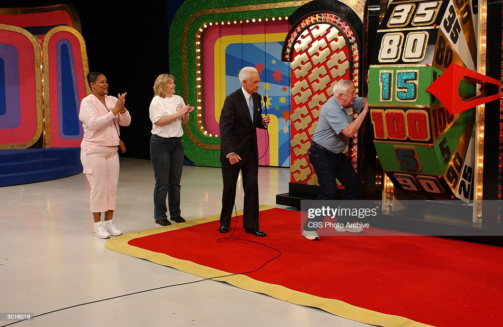 American television game show host Bob Barker watches contestant David Gorski spin the wheel along with Maxine Bryant and Susan Welch during the...