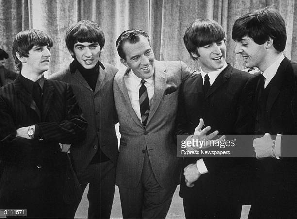 American television host Ed Sullivan smiles while standing with British rock group the Beatles on the set of his television variety series New York...
