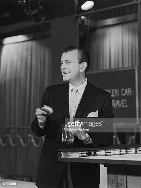 American television host Jack Paar smiles while holding a set of dentures and a glass on the set of an unidentified TV series circa 1955