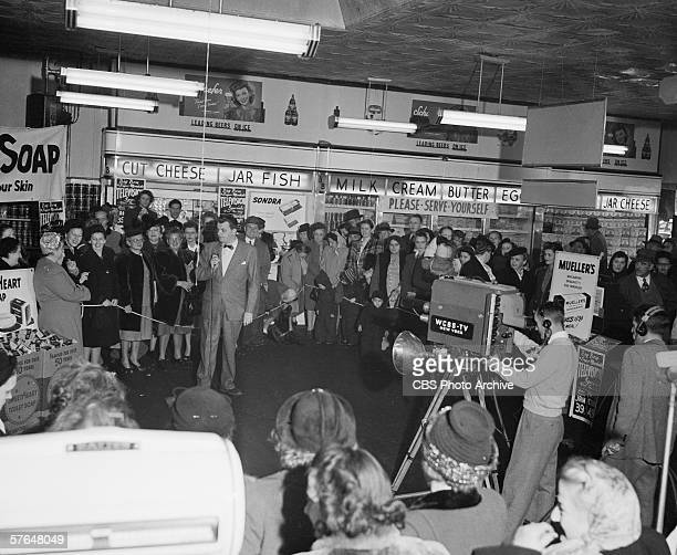 American television host John Reed King interviews female contestants in a grocery store as spectators watch filming of the CBS Television game show...