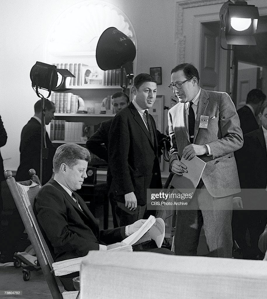 American television news producer Fred Friendly (1915 - 1998) (right), born Ferdinand Friendly Wachenheimer, holds documents and waits while American president <a gi-track='captionPersonalityLinkClicked' href=/galleries/search?phrase=John+F.+Kennedy+-+US+President&family=editorial&specificpeople=70027 ng-click='$event.stopPropagation()'>John F. Kennedy</a> (1917 - 1963) sits in a rocking chair and reads a paper and CBS News producer <a gi-track='captionPersonalityLinkClicked' href=/galleries/search?phrase=Don+Hewitt+-+Producer&family=editorial&specificpeople=214679 ng-click='$event.stopPropagation()'>Don Hewitt</a> looks on during the preparations for a broadcast from the White House, Washington, DC, 1963. Friendly quit CBS News in 1966 when the network decided to air an episode of 'I Love Lucy' instead of senate hearings into the Vietnam War.