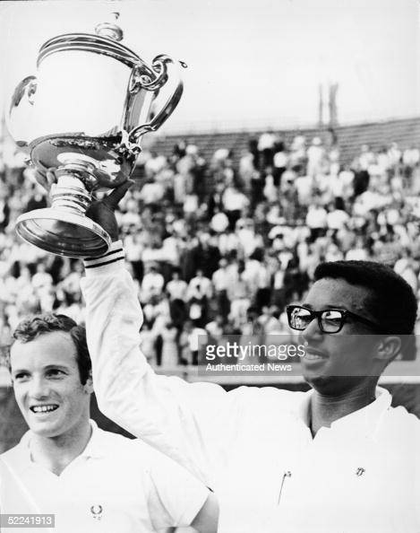 American tennis player Arthur Ashe holds up his trophy after winning the first ever US Open as his opponent Tom Okker of the Netherlands looks on and...