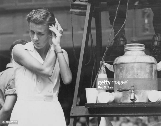 American tennis player Doris Hart fixes her hair between sets during her match against Zsuzsa Kormoczy of Hungary at Wimbledon London 30th June 1953