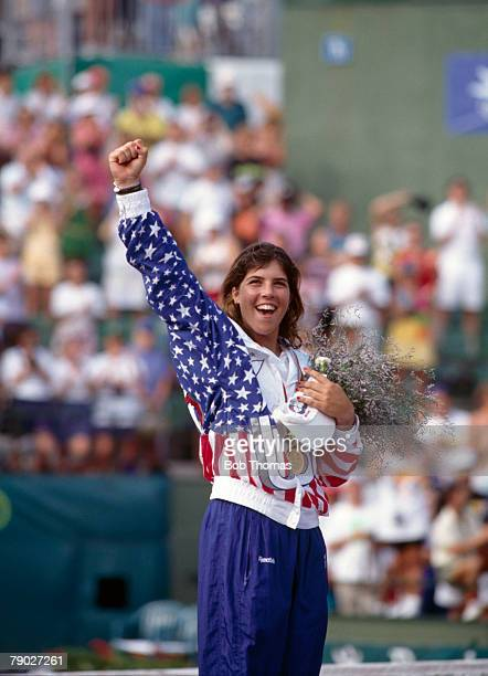American tennis player Jennifer Capriati of the United States team celebrates on the medal podium after finishing in first place by beating Steffi...