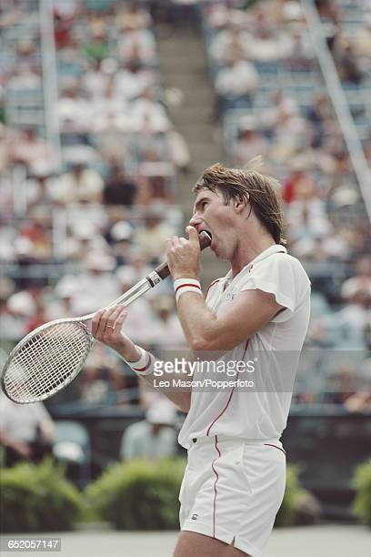 American tennis player Jimmy Connors bites the handle of his tennis racket during competition to reach the semifinal of the 1984 US Open Men's...