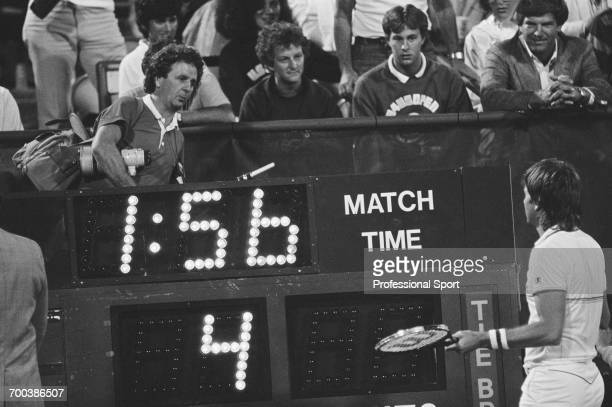 American tennis player Jimmy Connors pictured shouting at English photographer Tommy Hindley who is moving behind the scoreboard during competition...