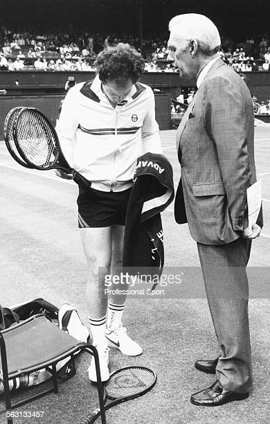 American tennis player John McEnroe being spoken to by Peter Morgan an official with the All England Tennis Club concerning his shorts breaking the...