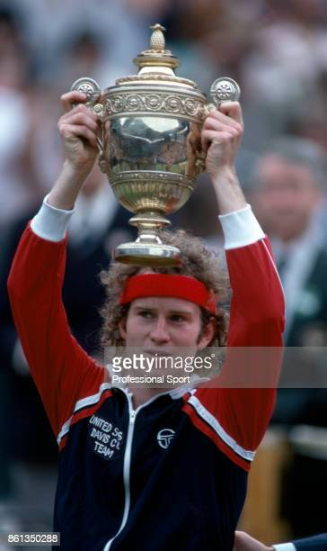 John McEnroe of the USA lifts the trophy after defeating Bjorn Borg of Sweden to win the Wimbledon Lawn Tennis Championships at the All England Lawn...