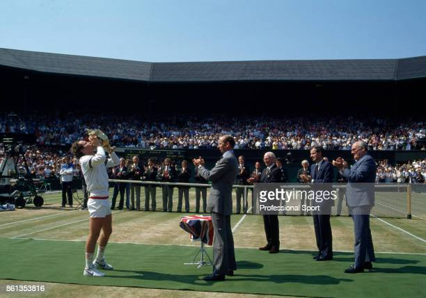 John McEnroe of the USA in action kisses the trophy after defeating Chris Lewis of New Zealand to win the Wimbledon Lawn Tennis Championships at the...
