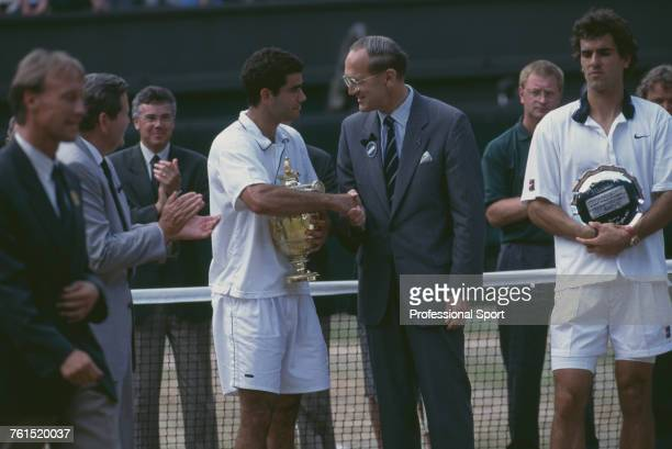 American tennis player Pete Sampras holding the Gentlemen's Singles Trophy is congratulated by Sir Geoffrey Cass President of the Lawn Tennis...