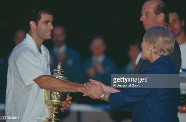 American tennis player Pete Sampras holds the Gentlemen's Singles Trophy as he shakes hands with Katharine Duchess of Kent after beating Australian...