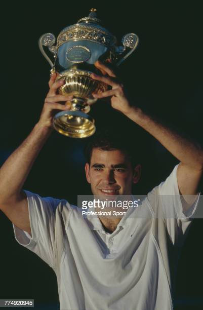 American tennis player Pete Sampras holds the Gentlemen's Singles trophy above his head after beating Australian tennis player Pat Rafter 67 76 64 62...
