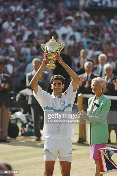 American tennis player Pete Sampras holds up the Gentlemen's Singles Trophy presented by Katharine Duchess of Kent after defeating fellow American...