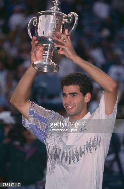 American tennis player Pete Sampras holds up the Men's Singles Trophy after beating fellow American Jim Courier 76 76 36 63 to win the final of the...
