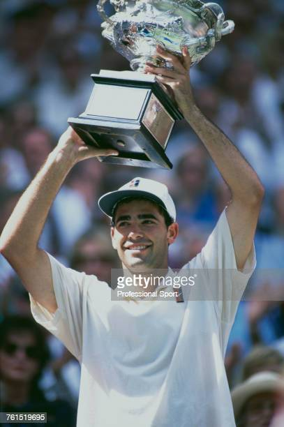 American tennis player Pete Sampras pictured holding the Norman Brookes Challenge Cup trophy in the air in celebration after beating Spanish tennis...