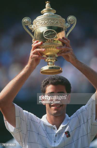 American tennis player Pete Sampras raises the Gentlemen's Singles Trophy in the air in celebration after beating Boris Becker of Germany to win the...