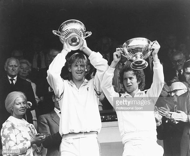 American tennis players John McEnroe and Peter Fleming lift their trophies in the Royal Box after winning the Men's Doubles Competition at Wimbledon...