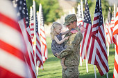 3 year old  girl running with her military dad who is wearing an American Army uniform in a field of American flags.