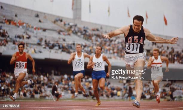 American track and field athlete Bill Toomey of the United States team competes in the 100 metres discipline prior to finishing in first place to win...