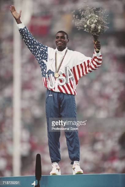 American track and field athlete Carl Lewis of the United States team celebrates on the medal podium after finishing in first place to win the gold...