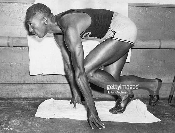 American track and field athlete Jesse Owens crouches in starting position while preparing for a race He is wearing a singlet shorts and cleated...