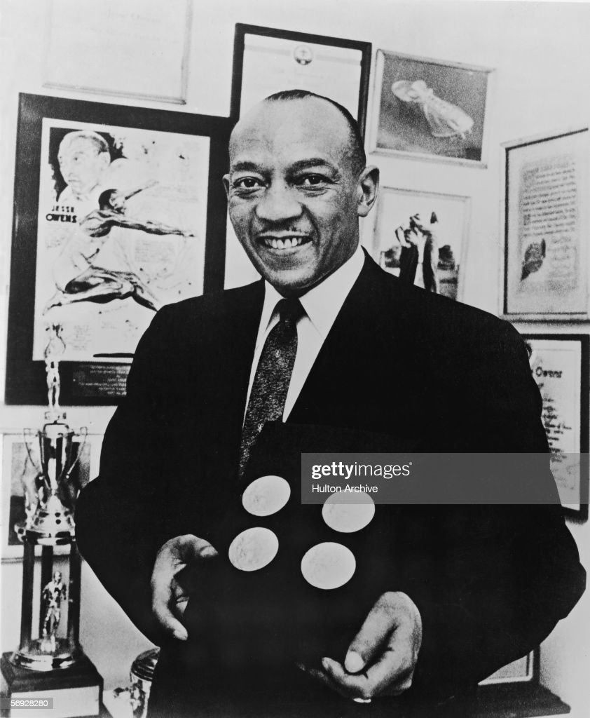 American track and field athlete Jesse Owens (1913 - 1980) smiles as he poses with the four gold medals he won at the 1936 Berlin Olympics, late 1950s.