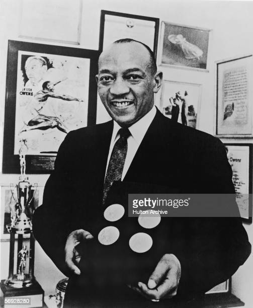 American track and field athlete Jesse Owens smiles as he poses with the four gold medals he won at the 1936 Berlin Olympics late 1950s