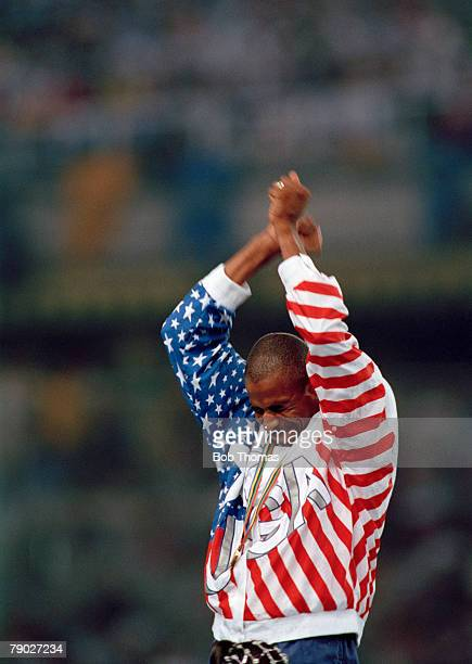 American track and field athlete Mike Conley Sr of the United States team raises his arms in the air in celebration on the medal podium after...